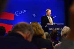 A man speaks at a podium during a No Labels conference