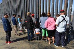 A group of people wait on one side of a large fence, looking through