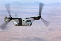 An Osprey helicopter flies over the desert
