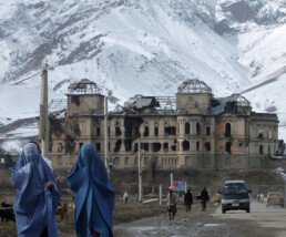 Two Afghan women walk with a damaged palace in the background