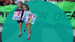 A protest march for climate change with two children leading the way