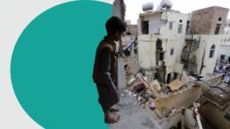 A small boy surveys wreckage from a bombing